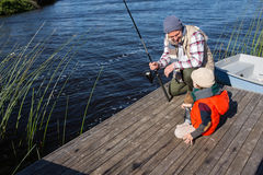 Happy man fishing with his son Stock Photos