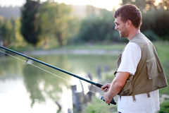 Happy man fishing in a pond Stock Images