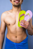Happy man with flip-flops going to the beach. Smiling young man with flip-flops going to the beach Royalty Free Stock Photography
