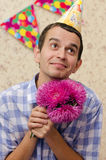 Happy man with flowers. A man asks for forgiveness with pink flowers in his hands royalty free stock photography