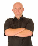 Happy man with folded arms. Half body portrait of middle aged bald man in black shirt with folded arms, white studio background Stock Image