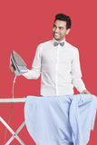 Happy man in formals ironing shirt over red background Royalty Free Stock Images