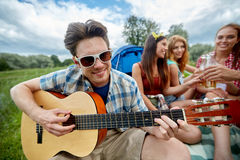 Happy man with friends playing guitar at camping Stock Photos