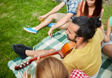 Happy man with friends playing guitar at camping Stock Photo