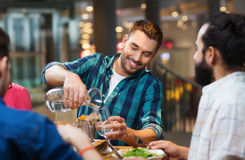 Happy man with friends pouring water at restaurant. Leisure, people and holidays concept - smiling men with friends pouring water from jug at restaurant Stock Image