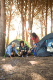 Happy man with friends setting up tent on field Stock Images