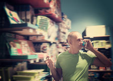 Happy man in front of difficult choice in store Royalty Free Stock Photos