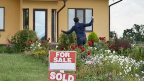 Happy man in front of their new house.  stock footage