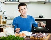 Happy man frying squid rings Stock Image