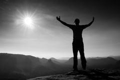 Happy man gesture in red cap of triumph with hands in the air. Funny hiker on the peak of sandstone rock in Saxony Switzerland par Royalty Free Stock Images