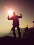 Happy man gesture of triumph. Funny hiker on the peak of sandstone rock in national park Saxony Switzerland watching into camera Stock Photo