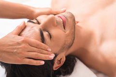 Happy man getting facial treatment at massaging center. Relaxed young guy is enjoying massage at spa. He is resting and smiling. Masseuse is touching his Royalty Free Stock Photos