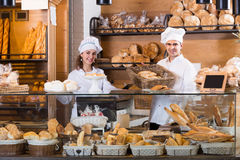 Happy man and girl selling pastry and loaves. Happy men and girl selling fresh pastry and loaves in bread section royalty free stock photo