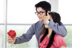 Happy Man Gives A Gift to Young Woman Royalty Free Stock Photography