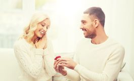 Happy man giving engagement ring to woman at home. Love, couple, relationship, proposal and holidays concept - happy men giving engagement ring in little red royalty free stock photography