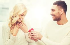 Happy man giving engagement ring to woman at home. Love, couple, relationship, proposal and holidays concept - happy men giving engagement ring in little red royalty free stock images