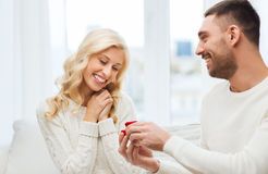 Happy man giving engagement ring to woman at home Stock Photo