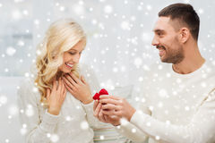 Happy man giving engagement ring to woman at home. Love, couple, relationship, proposal and holidays concept - happy men giving engagement ring in little red stock image