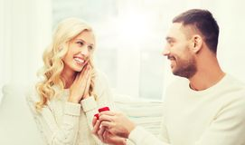 Happy man giving engagement ring to woman at home. Love, couple, relationship, proposal and holidays concept - happy men giving engagement ring in little red royalty free stock image