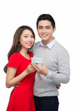 Happy Man giving a gift to his Girlfriend. Happy Young beautiful Couple isolated on a White background. Royalty Free Stock Images