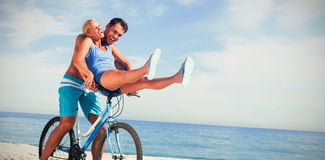 Happy man giving girlfriend a lift on his crossbar Royalty Free Stock Photos