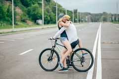 Happy man giving girlfriend a lift on his crossbar of bike on the beach Royalty Free Stock Image