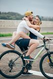 Happy man giving girlfriend a lift on his crossbar of bike on the beach Royalty Free Stock Images