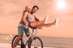 Happy man giving girlfriend a lift on his crossbar Stock Photo