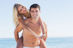Happy man giving his pretty girlfriend a piggy back smiling at c Royalty Free Stock Photography