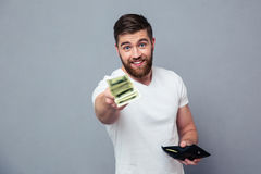 Happy man giving money at camera. Portrait of a happy casual man giving money at camera over gray background royalty free stock photo