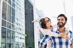 Happy man giving piggyback ride to woman in city Stock Image