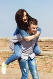 Happy man giving piggyback ride to woman Royalty Free Stock Photos