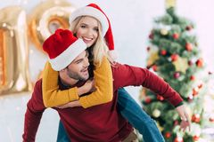 happy man giving piggyback to his smiling girlfriend stock photos