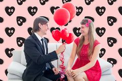 Happy man giving red balloons to woman. Against digitally composite heart background Royalty Free Stock Image