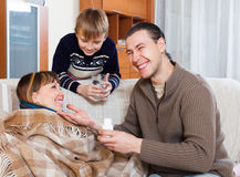 Happy man giving  tablets to unwell wife Stock Images