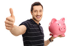 Happy man giving a thumb up and holding a piggybank. Isolated on white background Stock Photography