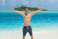 Happy man giving thumbs up sign at beach Royalty Free Stock Photo
