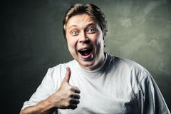 Happy man giving thumbs up sign on gray Royalty Free Stock Photo