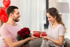 Happy man giving woman flowers and present at home stock image