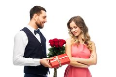 Happy man giving woman flowers and present royalty free stock image