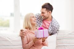 Happy man giving woman gift box at home Royalty Free Stock Photography