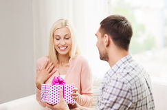 Happy man giving woman gift box at home Royalty Free Stock Images