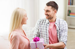 Happy man giving woman gift box at home Stock Image
