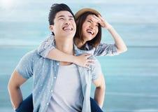 Happy man giving woman piggyback on beach Royalty Free Stock Photos