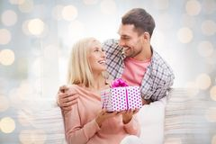 Happy man giving woman present over holiday lights Royalty Free Stock Image