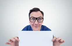 Happy man in glasses holds a sheet in front of white paper Stock Image