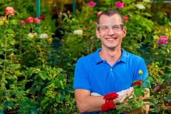 Happy man with glasses and laboratory gloves in a greenhouse Stock Photo