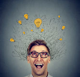 Happy man in glasses looking up with light idea bulb above head Royalty Free Stock Photos