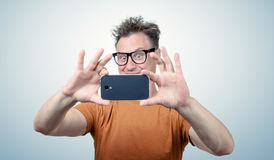Happy man in glasses photographed by smartphone Royalty Free Stock Photo