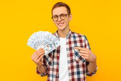 Happy man in glasses and a plaid shirt, with dollar bills, on yellow background royalty free stock photos